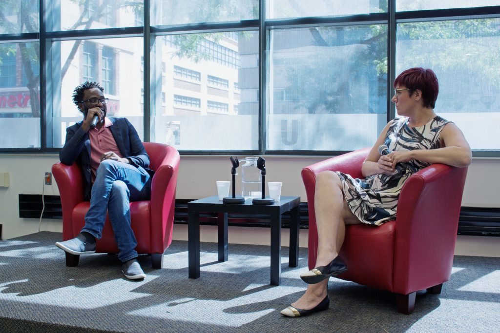 "Ugandan director Kamoga Hassan discusses his film, ""Outed: The Painful Reality,"" with journalist and queer media instructor Andrea Houston. Photo courtesy Jessica Ross."