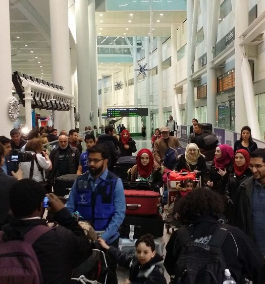 A family from Syria arrives in Toronto. Image courtesy of Domnic Santiago/CC BY 2.0.